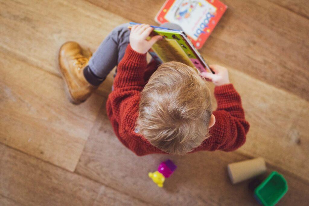 Lille dreng på gulvet med en bog i hænderne