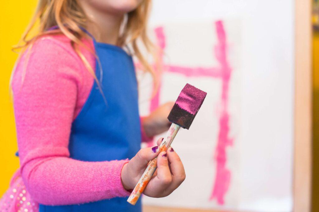 Lille pige med lyserød trøje og blåt forklæde med malersvamp i hånden